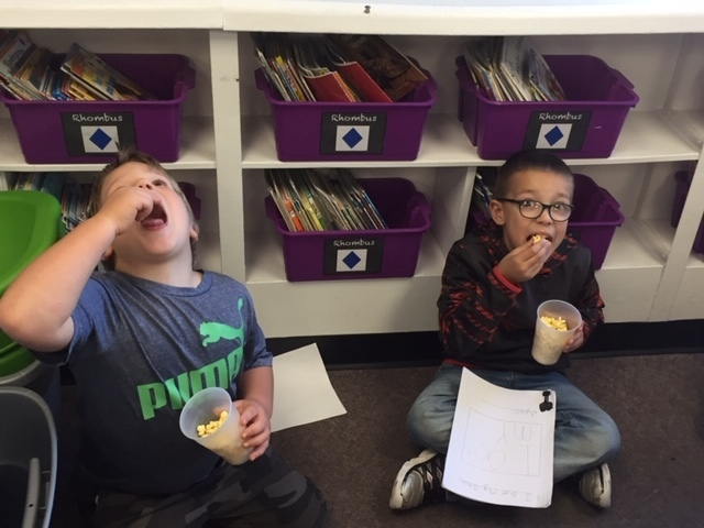 First and second grade students enjoy a snack after sharing their writing.